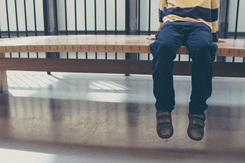 chlapec sediaci na lavicke